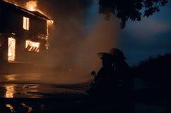 Brandmän som tämjer eldsvåda Royaltyfri Fotografi
