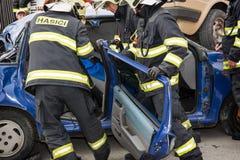 Brandmän som tar bort de bitande dörrarna från en bil, havererar Royaltyfri Foto
