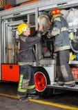 Brandmän som tar bort slangen från lastbilen Arkivbilder