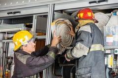 Brandmän som tar bort vattenslangen från lastbilen Arkivfoton