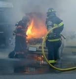 Brandmän som ut sätter en bil på brand Fotografering för Bildbyråer