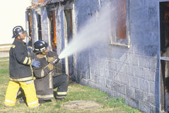 Brandmän som ut sätter ett hus på brand Fotografering för Bildbyråer