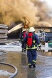 Brandmän stöttar för att gå kampen växtbranden Arkivfoto