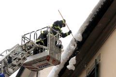 Brandmän tar bort snow från eavesna Royaltyfri Foto