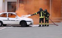 Brandmän under övningen som släcker en brand i en bil Royaltyfri Bild