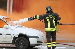 Brandmän under övningen som släcker en brand i en bil Royaltyfria Bilder