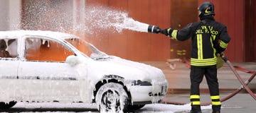 Brandmän under övningen som släcker en brand i en bil Royaltyfria Foton