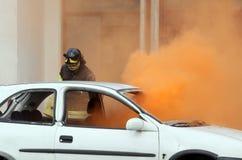 Brandmän under övningen som släcker en brand i en bil Arkivbild