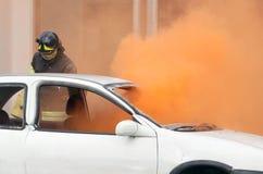 Brandmän under övningen som släcker en brand i en bil Royaltyfri Fotografi