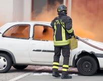 Brandmän under övningen som släcker en brand i en bil Arkivfoto