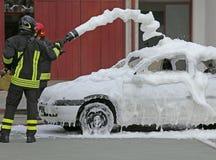 Brandmän under övningen som släcker en brand i en bil Arkivfoton