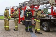Brandmännen kontrollerar deras utrustning royaltyfria foton