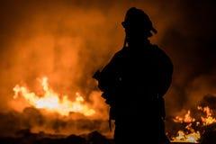 Brandman Battling Structure Fire Fotografering för Bildbyråer