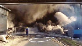 Brandman framme av en stor brandbrand - släcka Fotografering för Bildbyråer