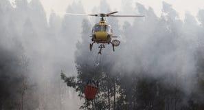 Brandman Helicopter Dropping Water för borgerligt skydd för portugis CS-HMI på en brand arkivbilder