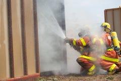 Brandman i dräkt för brandskydd som besprutar vatten för att avfyra surro Arkivbilder