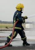 Brandman med slangen Arkivfoto