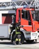 Brandman och en firetruck i barackerna av brandkåren Arkivfoton