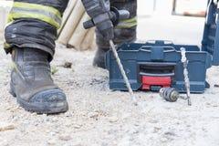 Brandman som arbetar med en drillborr royaltyfria foton