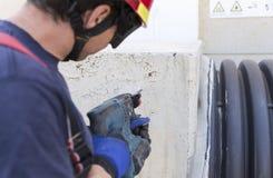 Brandman som arbetar med en drillborr royaltyfria bilder