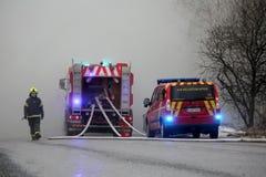 Brandman som dyker upp från rök med brandlastbilar på gatan Arkivbild