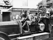 Brandman som kör en brandmotor och ett sammanträde för ung kvinna bredvid honom (alla visade personer inte är längre uppehälle oc Royaltyfri Foto