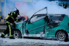 Brandman som räddar offret för bilolycka i bränd bil royaltyfri fotografi