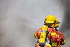 Brandman två i dräkt för brandstridighet som besprutar vatten för att avfyra och Arkivbilder
