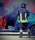 Brandman under avstängning av en brand av en bil Arkivfoto