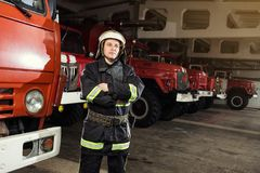 Brandmanbrandman i handlinganseende nära en firetruck Emer Royaltyfri Bild
