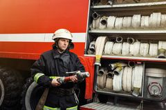 Brandmanbrandman i handlinganseende nära en firetruck Emer Arkivbilder