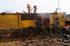 Brandmanfullföljande som släcker huset Royaltyfria Foton