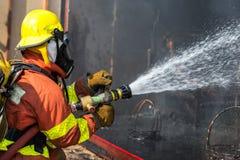 Brandmanhållen och justerar dysa- och brandslangen som besprutar vatten Royaltyfri Foto