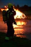 Brandmannen förbereder sig att vattna med slang en brand på natten Royaltyfri Bild
