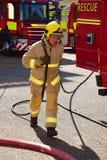 Brandmannen kör ut en slang på platsen av en brand Royaltyfri Bild