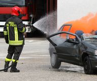 Brandmannen med hjälmen av bilen brände med skumet Fotografering för Bildbyråer