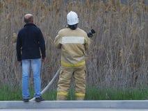 Brandmannen och mannen ser någonstans royaltyfri foto