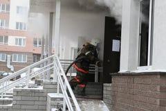 Brandmannen skriver in till den rökande dörren Arkivbilder