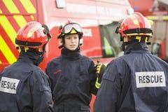 brandmannen som ger henne anvisningar, team till Royaltyfria Bilder