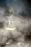 Brandmannen som ner vattnar med slang och fuktar i en rök, fyllde byggnad Royaltyfri Fotografi