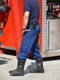 Brandmannen står bredvid en firetruck Arkivfoton