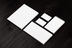 Brandmerkende kantoorbehoeften, modelscène op zwarte houten plank, lege voorwerpen voor het plaatsen van uw ontwerp stock foto