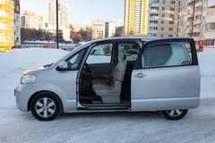 Brandmerkt het familie ruime auto zijaanzicht van Toyota porte in grijs met een geopende automatische deur buiten in de winter, m stock afbeelding