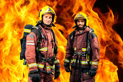 Brandmän mot brinnande bakgrund Arkivbild