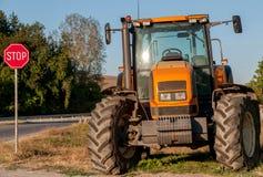 Brandnew orange traktor på slutet av byn Arkivfoto
