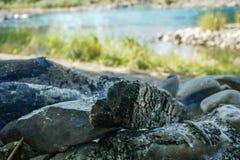 Brandplaats met hout en as dichtbij rivier stock fotografie
