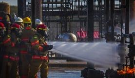 Brandskolautbildning med levande brand och brandmannen Royaltyfri Foto