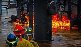 Brandskolautbildning med levande brand och brandmannen Royaltyfri Bild