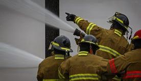 Brandskolautbildning med levande brand och brandmannen Royaltyfria Bilder