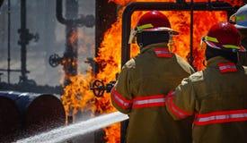 Brandskolautbildning med levande brand och brandmannen Fotografering för Bildbyråer
